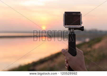 hand holding extreme camera taking landscape photo at sunset