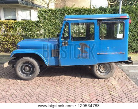 Hilversum, The Netherlands - March 5, 2016: U.S. Mail Postal Dispatcher Jeep parked by the side of the road in the city of Hilversum. Nobody inside inside the vehicle