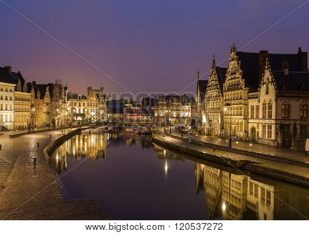 A view of beautiful old buildings along Korenlei Graslei and the River Leie in Ghent Old Town at night. Reflections can be seen in the water.