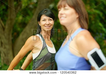 Couple of technology savy women in their forties preparing for a run by streching their muscles