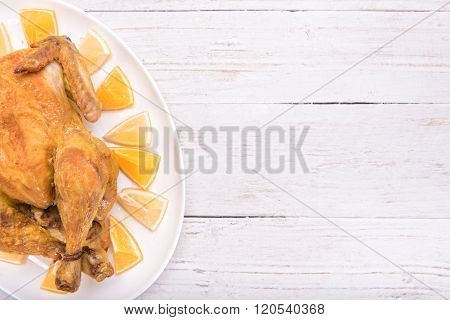 Roasted chicken with lemon and orange. Background.
