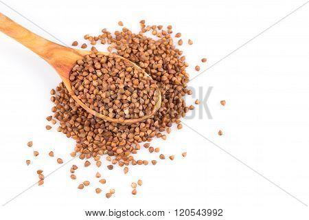 Uncooked buckwheat on wooden spoon. premium buckwheat groats on white background poster