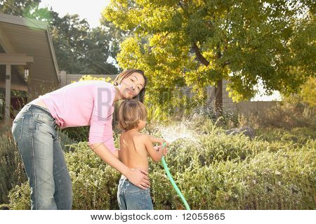 Mother and young son watering plants with hose