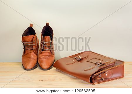 Still life with Brown leather shoes with leather bag on wooden table