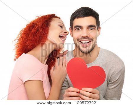 Happy young couple in love holding red paper heart and having fun together, isolated on white
