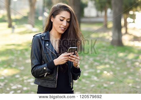 Young Woman Using A Smartphone In An Urban Park