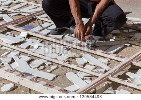 Man Worker Repairing Steel Fence With Electric Saw Tool