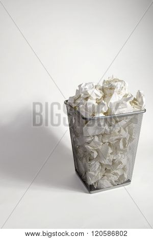 A Waste Paper Bin With Screwed Up Paper