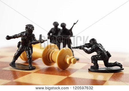 War concept. Toy soldiers kill chess King. Death of king.