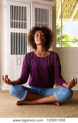 African American Woman Practising Yoga At Home