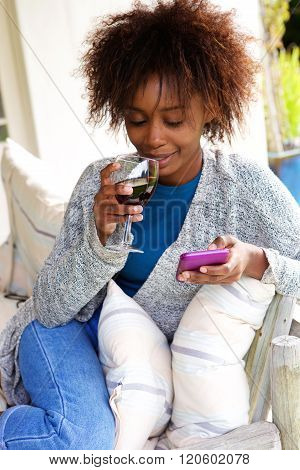 Young Woman Drinking And Using Cell Phone
