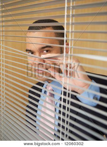 Businessman peering through blinds