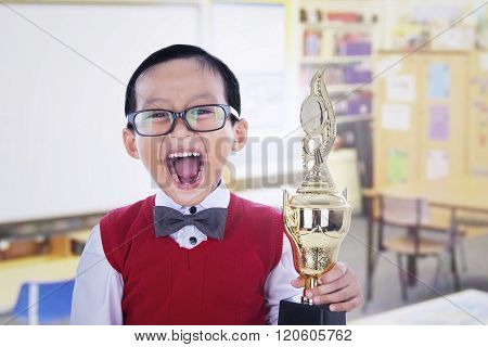 Excited Student Boy Holding Trophy At Library
