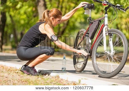 Young Woman Checking Her Bicycle In Park