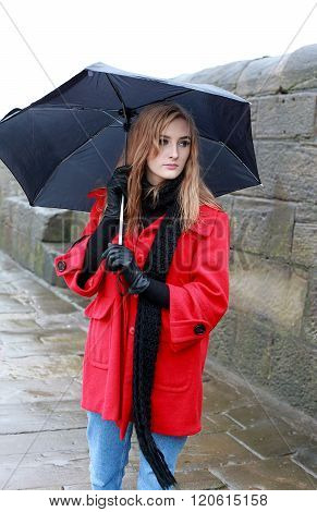 Young Woman Holding An Umbrella From Sleet And Rain