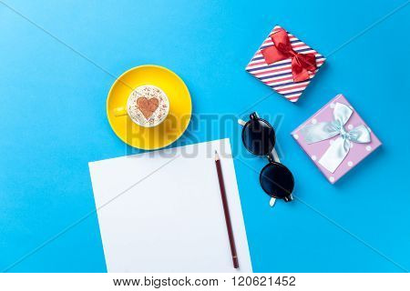 Paper, Cup, Glasses And Gifts Lying On The Table