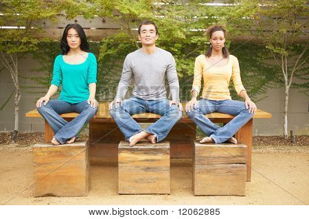 Three friends sitting on table with feet on benches outdoors