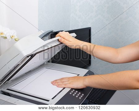 Woman's hand with working copier at home