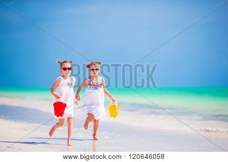 Adorable little girls have fun on the beach