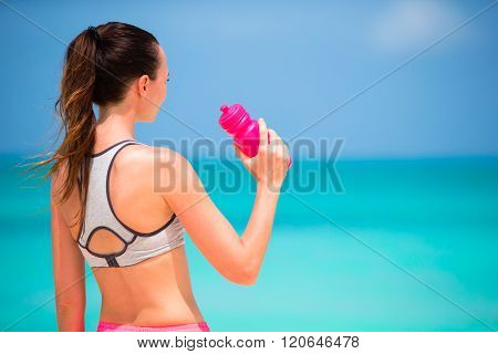 Fit active young woman drink water on white beach