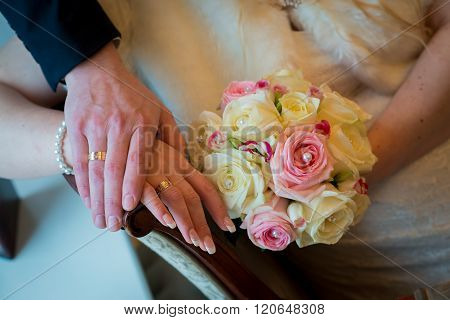 Hands and rings with beautiful wedding bouquet