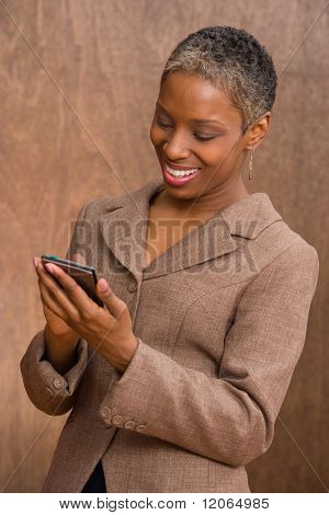 Businesswoman writing in palm pilot