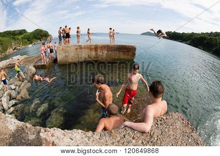 NAKHODKA, RUSSIA - CIRCA AUGUST, 2015: Joyful children jumping and diving into the sea from the old dock. Local children love to relax, sunbathe, swim and dive in the sea bay near the Nakhodka city