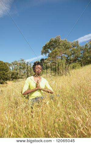 Woman meditating in field
