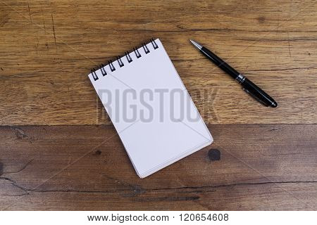 Notebook on wooden table with pen on side