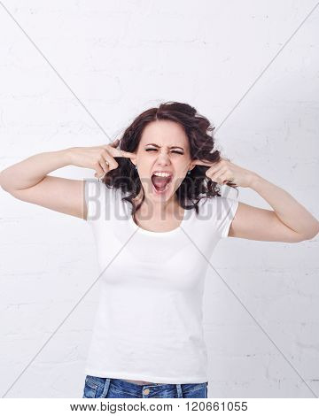 Girl Screams, Covering Ears With Her Hands.