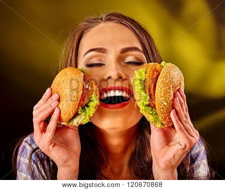 Happy girl keeps big woman small hamburgers. Fastfood concept on green.