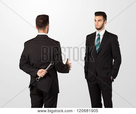 Two opposing businessman shake hands, one of them hiding a weapon behind his back