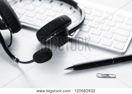 Office desk with headset and pc. Call center support table. Blue toned