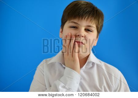 Teenage boy with a toothache on light background