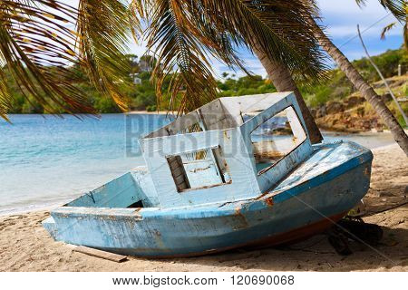 Old wooden boat at tropical beach with palm trees, white sand, turquoise ocean water and blue sky at Antigua Island in Caribbean