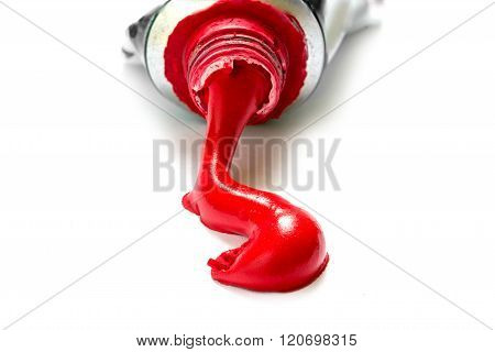 Red Paint Color Flowing Out Of A Tube, Closeup Isolated With Shadows On A White Background, Copy Spa