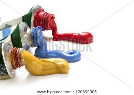 Paint Colors In Yellow, Blue And Red Flowing From The Tubes, Closeup On  White With Copy Space