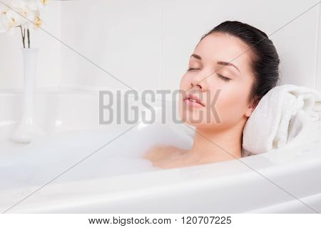 young beautiful brunette woman takes bubble bath poster