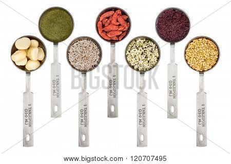 superfood abstract  background - macadamia nuts,  barley grass powder,  white chia seeds, goji berry, hemp seeds, acai berry and golden flax seeds - top view of  metal measuring tablespoons on white