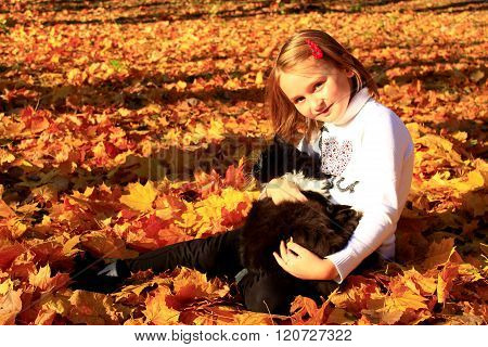 Little Girl Plays With Her Cat In The Autumn Park