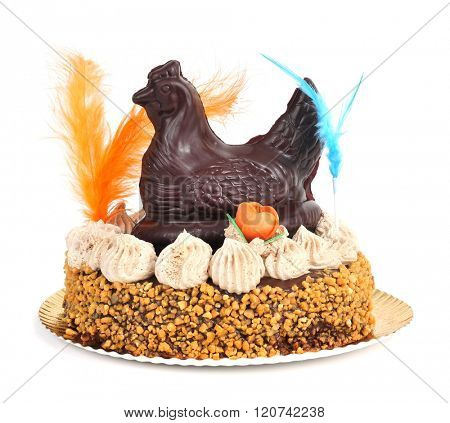 a mona de pascua, a cake eaten in Spain on Easter Monday, ornamented with feathers and a chocolate chicken, on a white background