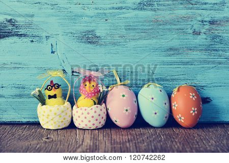 a funny couple of teddy chicks, a male and a female, and some different ornamented easter eggs on a wooden surface, against a blue rustic wooden background