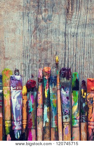 Row Of Artist Paint Brushes Closeup On Old Rustic Wooden Background.