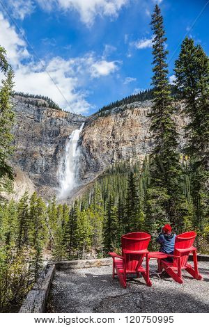 The woman photographs the famous waterfall. Two red deck chairs to relax in front of the waterfall Takakkaw. Autumn day in Yoho National Park in the Rocky Mountains