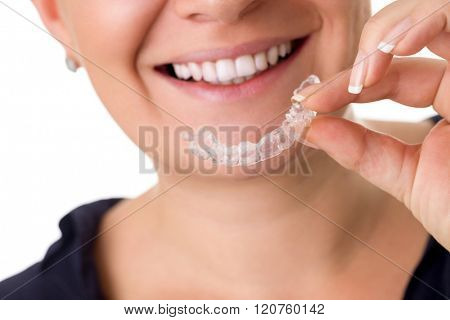 Woman with perfect teeth holding invisible braces, correction teeth braces for night