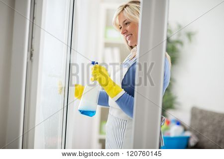 Young housemaid use liquid with spray for windows