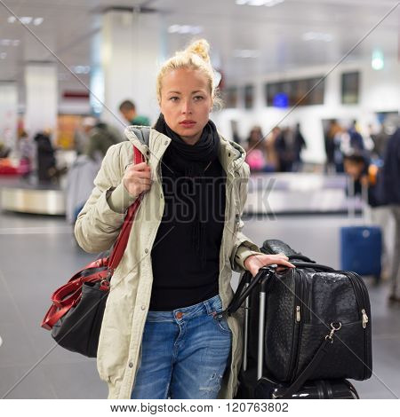 Female traveler transporting her luggage in airport terminal.