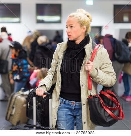 Female traveller waiting for luggage in airport terminal.