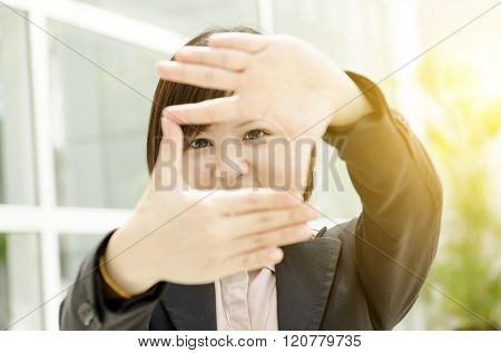 Young Asian business woman creating frame with fingers, at an office environment, natural golden sunlight at background.