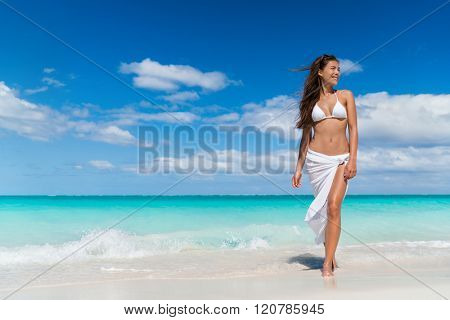Beach woman in fashion beachwear white cover-up skirt clothing. Asian girl tourist wearing white pareo for sun protection relaxing walking in ocean water on summer vacation travel.